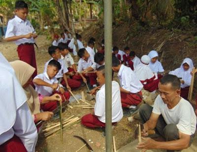 Langkah 2 pembuatan besek/piti membagi bambu menjadi belahan kecil kecil yang akan digunakan membuat iratan-iratan kecil