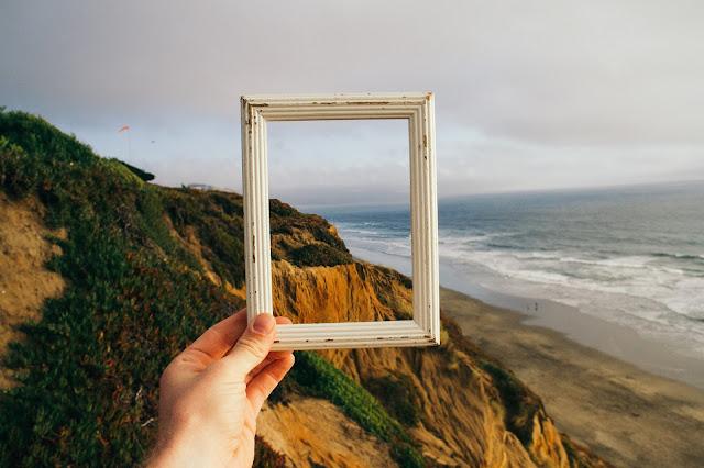 Photo by pine watt on Unsplash: Frame held up to coastal view
