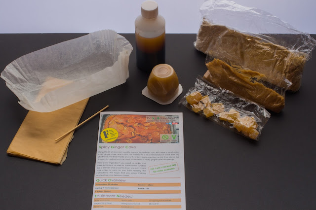 The contents of the baking kit laid out including instructions, bags with powder in, sugar, crystalised ginger, apple puree and a bottle containing brown liquid