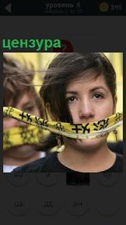 Девушке заматывают рот скотчем, таким образом цензура в действии