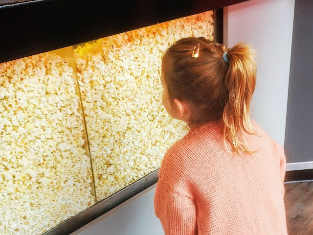 image of a young girl in a pink knitted cardigan staring longingly into a large vat of cinema popcorn.
