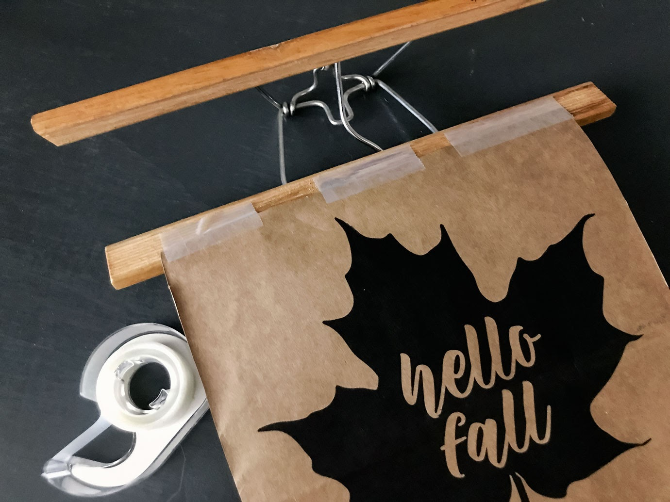 Taping the Hello Fall Printable to the hanger