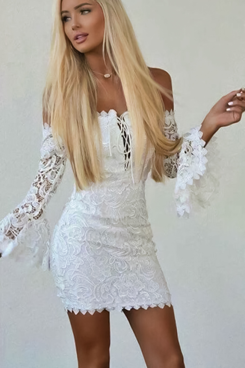 woman with long hair is posing on a plain background in a short boho dress