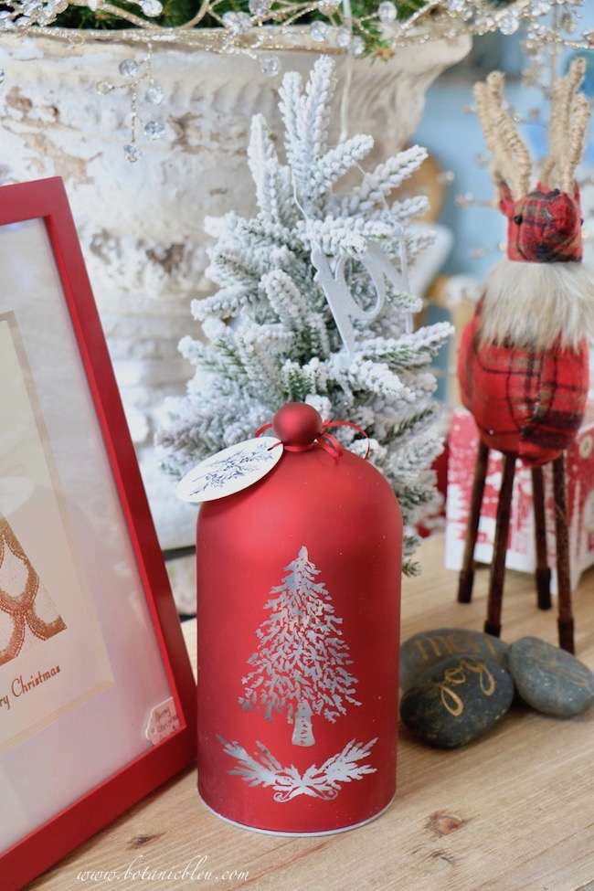 French Country Christmas Event 2019 has a red bell-shaped LED light that uses batteries to power a flickering light through a silver etched tree design