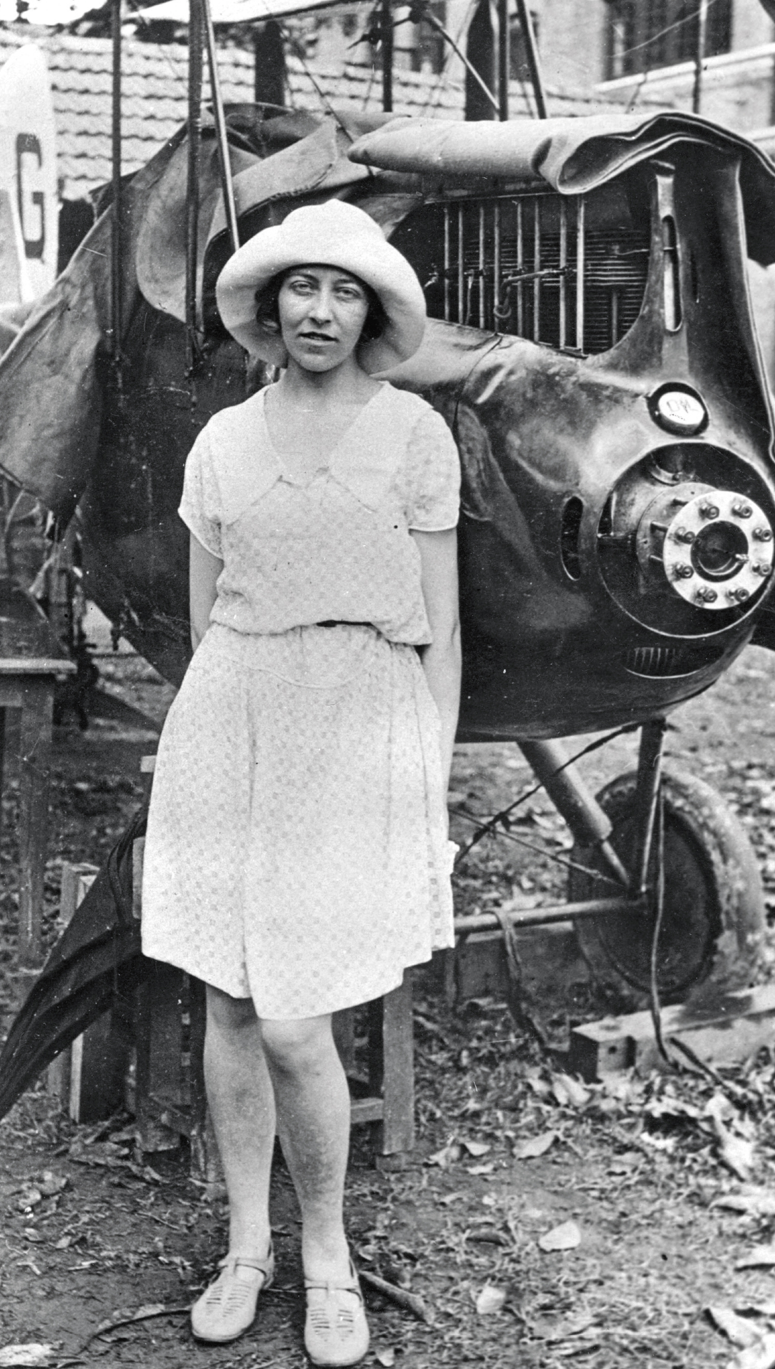 British Pilot Amy Johnson standing with a plane