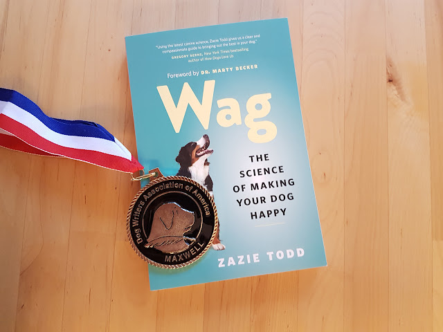 A copy of Wag: The Science of Making Your Dog Happy, pictured with the Maxwell Medallion it won from the Dog Writer's Association of America