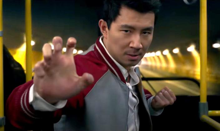 Imagem de capa: o ator Simu Liu, um homem asiático de cabelos pretos curtos, em um ônibus em movimento, com uma jaqueta vermelha com detalhes brancos e uma camisa branca por baixo, fazendo uma pose de arte marcial e se preparando para lutar, enquanto olha para frente.