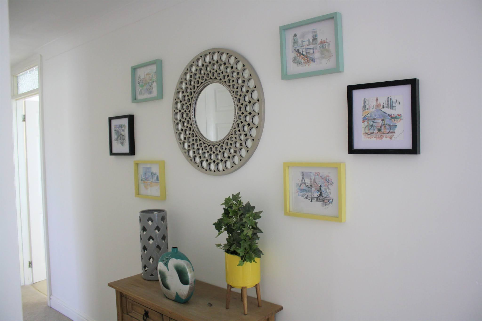 coloured prints in coloured frames by mirror, console table and hallway. coloured vases and plants at side