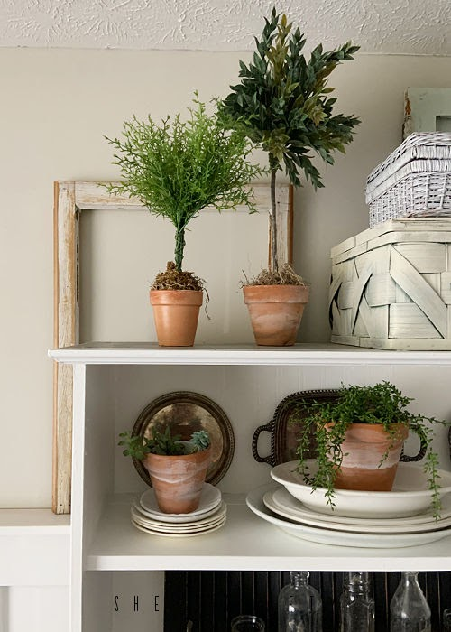 Spring Home Tour - living room white bookshelf with topiaries and windows.