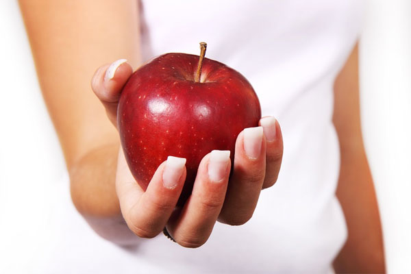 mulher segurando uma maçã