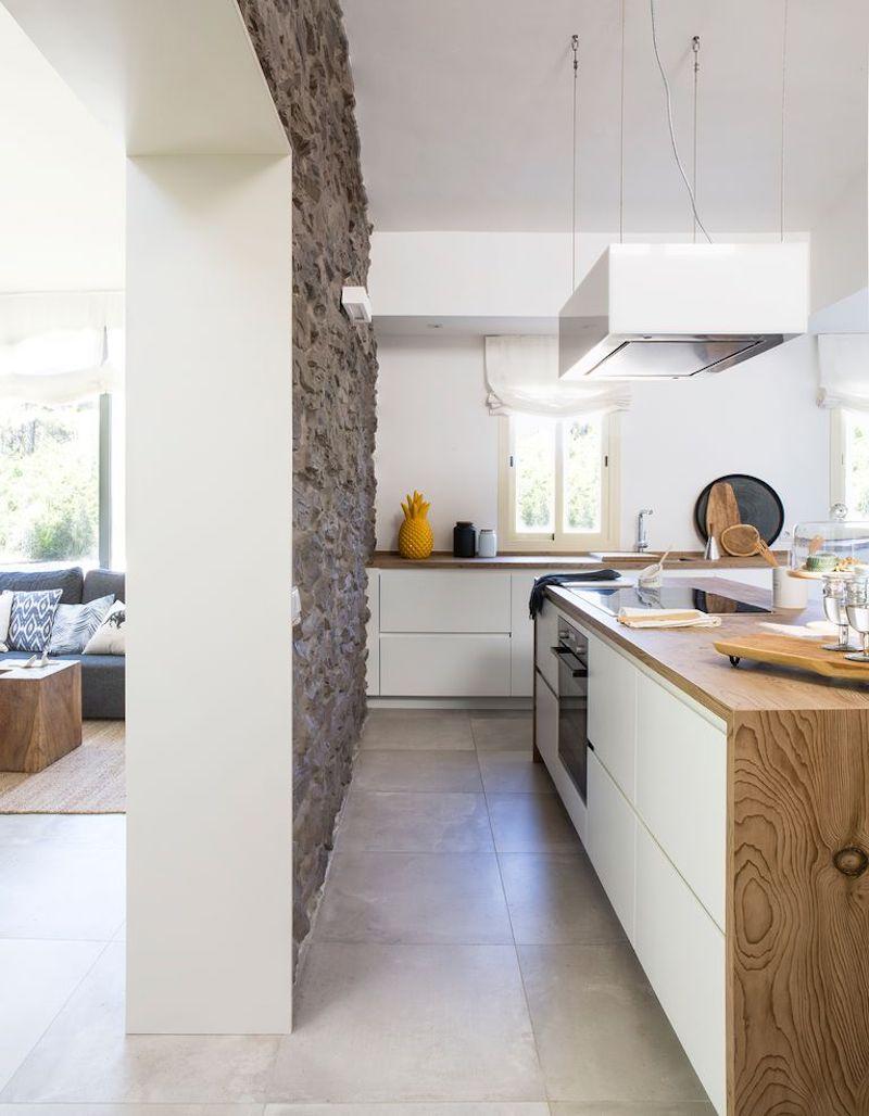 Cocina moderna blanca sin tiradores (detalle del porcelánico en el suelo de gran tamaño)