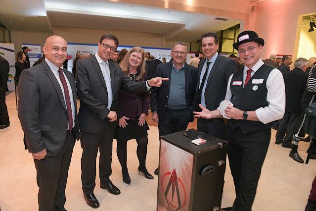 Mágico em uma foto com o público do evento de premiação Abigraf todos muito felizes e um deles sinalando o mágico.