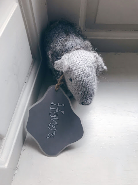 Small knitted sheep with a label around its neck