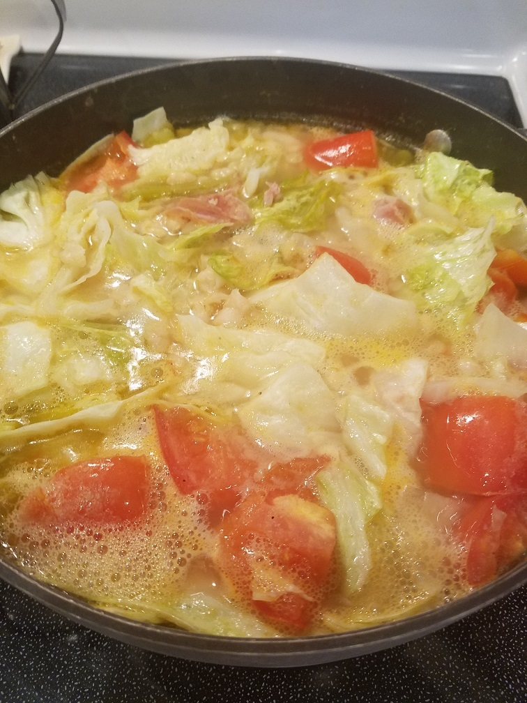 this is a huge soup pot Le Creuset with cabbage, ham, beans and tomatoes in it