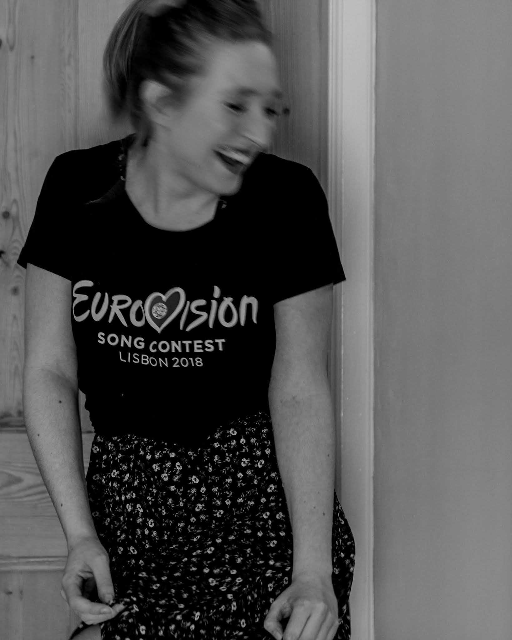 black and white photo of girl dancing in flowy floral dress and eurovision t shirt
