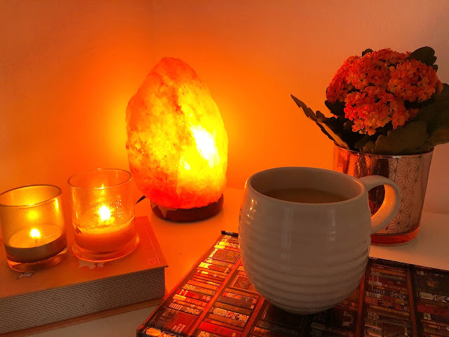 salt lamp next to two small candles and a cup of tea in white mug on top of notebook