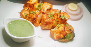 Tandoori paneer Tikka with green chutney, slice of onions and lemon wedges for paneer Tikka