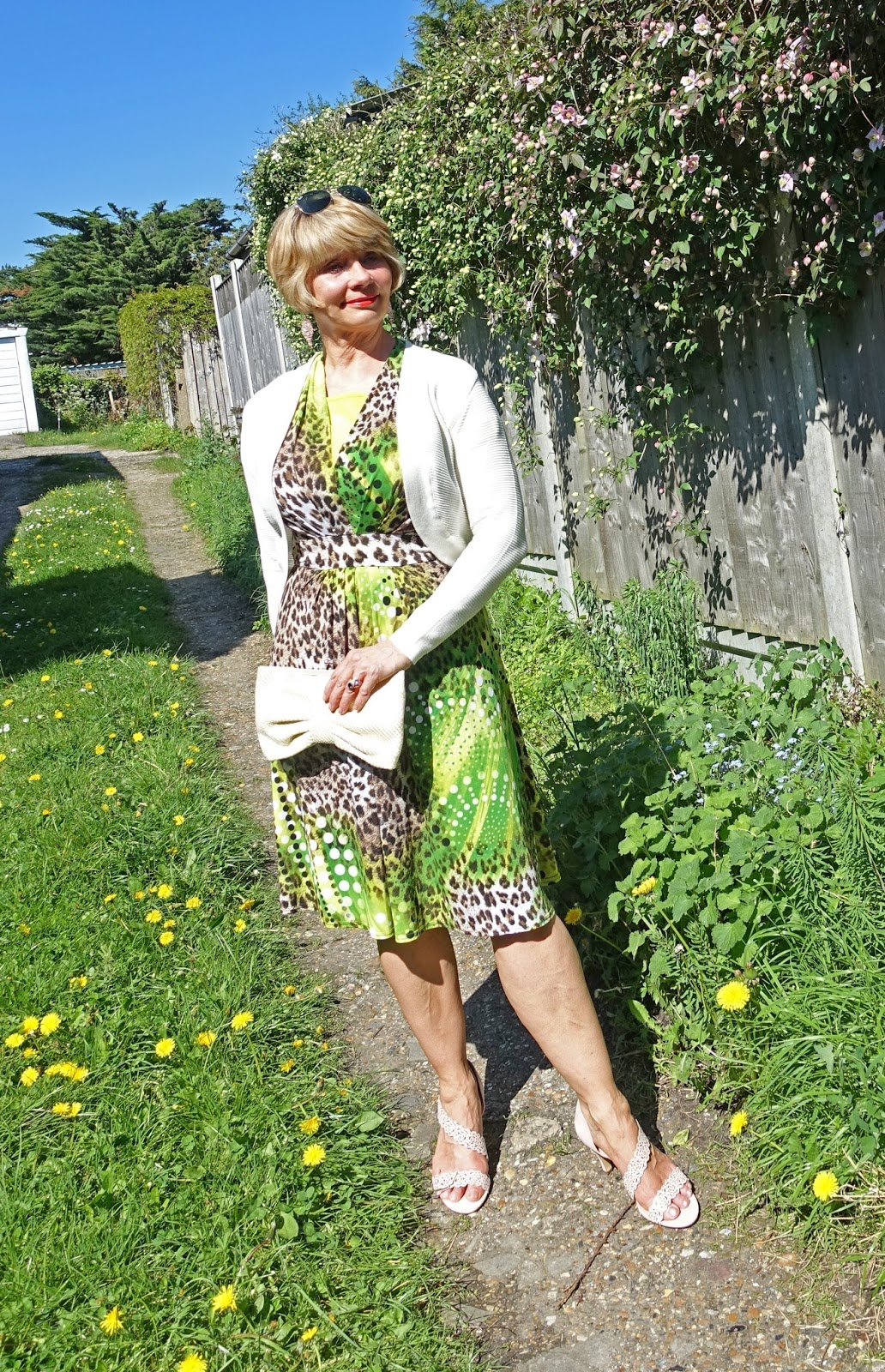 A cream bolero cover up and nude Lotus Cattleya sandals worn with a bright green and leopard print Joseph Ribkoff dress.