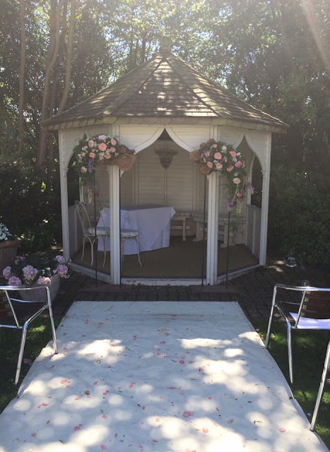 Outdoor British summer wedding with aisle and rose petals at Felix House Hotel Cambridge with Gazebo