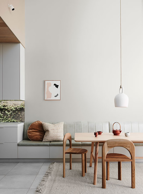 wall banquette in upholstered leather with dining table and white ceramic hanging pendant light