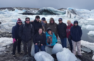 men and women stading in front of glacier