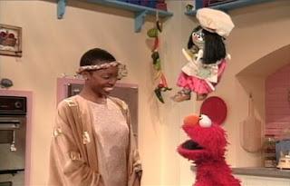 Jean the Genie summons Heather Headley as a Pocket Queen. Sesame Street Elmo's Magic Cookbook