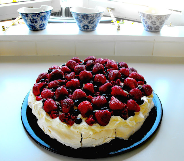 Real New Zealand pavlova with strawberries, raspberries, blueberries and cream