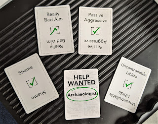 "Five game cards laid out with the Skills cards being ""Really bad aim, Passive Aggressive, Shame, and Uncontrollable Libido"".  The Job is ""Archaeologist."""