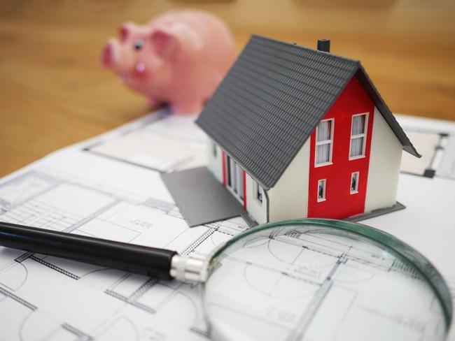 Imagem Mockup Maquete de Casa sobre um planta com um porquinho atrás