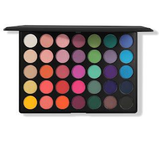 A black rectangular thick plastic case containing circular pans of different coloured eyeshadows including blue, pink, orange and green on a bright background