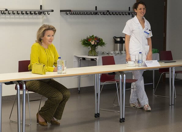 Queen Mathilde wore Natan yellow silk blouse and print pants. Natan clutch bag. Dries Van Noten print trousers