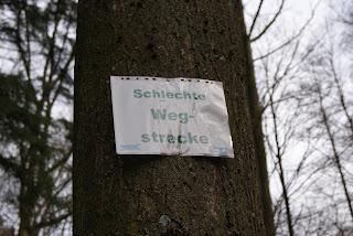 """An einem Baum hängt ein Schild mit der Aufschrift """"Schlechte Wegstrecke"""""""