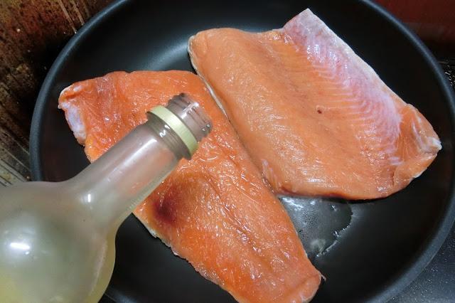 鮭を皮を下にしてフライパに並べ入れ、白ワインをまわしかけてから中火にかけます。  沸々としてきたら弱火~中火にし、ふたをして約15分蒸し焼きにします。