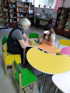 Бабушка с внучкой играют в шашки младший отдел читальный зал бібліотека-філія №4 М.Дніпро