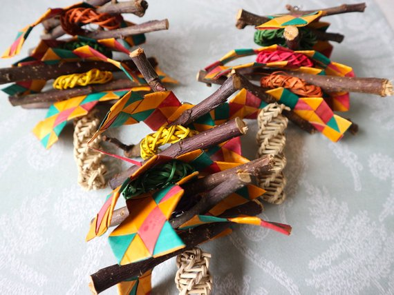 a chain strung with twisted pieces of wood, sticks, and brightly coloured squares of paper