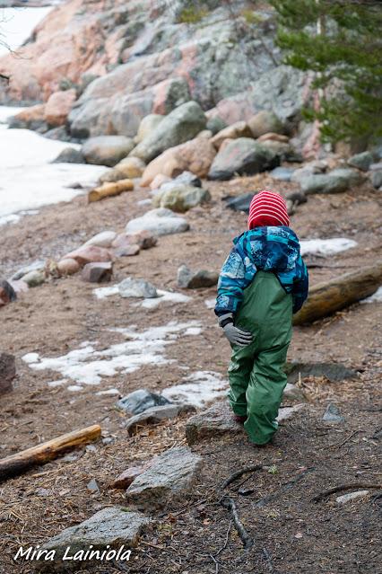 Nuori poika kulkee kurahousuissa rantahiekassa. Takana näkyy rantakallioita.
