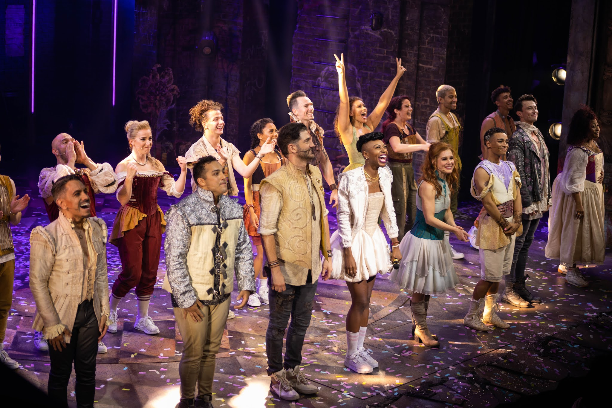 The cast of & Juliet the musical are on stage in the West end bowing and smiling.