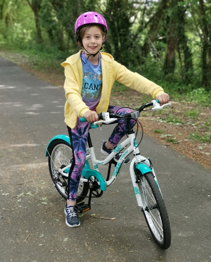 young girl wearing pink helmet and yellow jumper sitting on bike