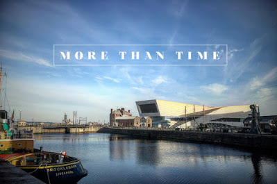 "A still from the film ""More Than Time"" showing a deserted scene at the Liverpool waterfront: a museum building, boats, docks, a blue sky, and no people."