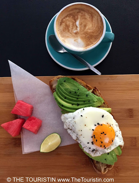 A flat white coffee in a light blue cup and pieces of watermelon and a piece of lime next to avocado and a sunny side up on sourdough bread.