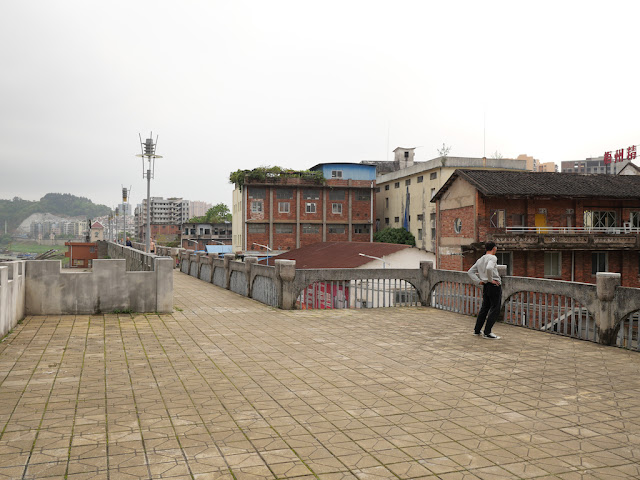 man stretching on a wall bordering the Gui River (桂江) in Wuzhou (梧州)