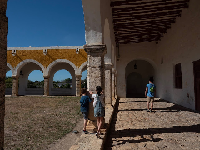 niños y hombre de espaldas paseando bajo los arcos del atrio del convento de San Bernardino en Izamal