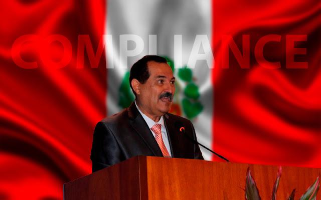 Enrique Medri Gonzales, habla frente a una bandera de Perú