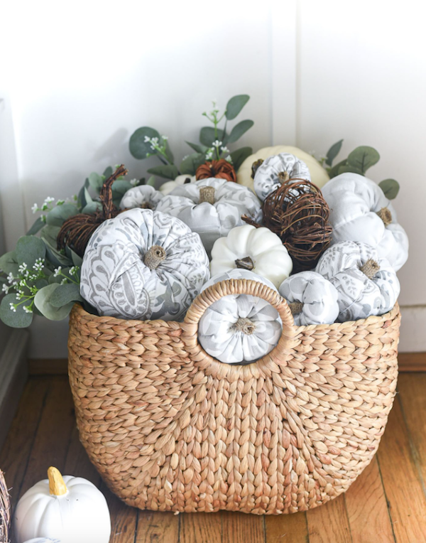 A wicker basket of white and grey farmhouse style fabric pumpkins