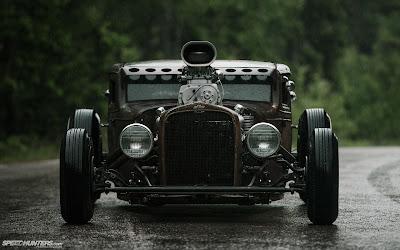 Cochazo con un motor brutal aparcado en carretera mojada