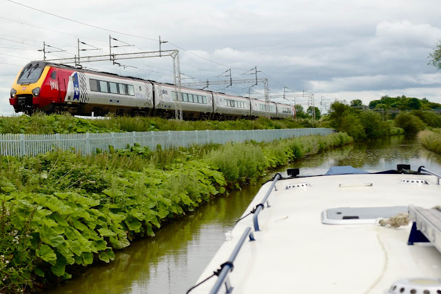 train passing a canal boat with trees and water and a cloudy sky
