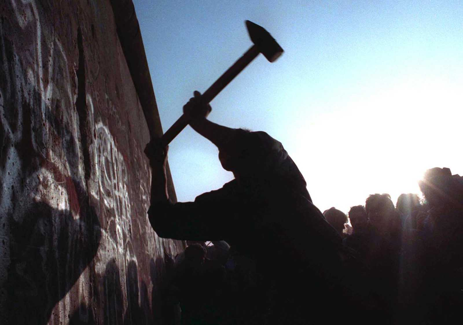 A man hammers away at the Berlin Wall on November 12, 1989 as the border barrier between East and West Germany was torn down.