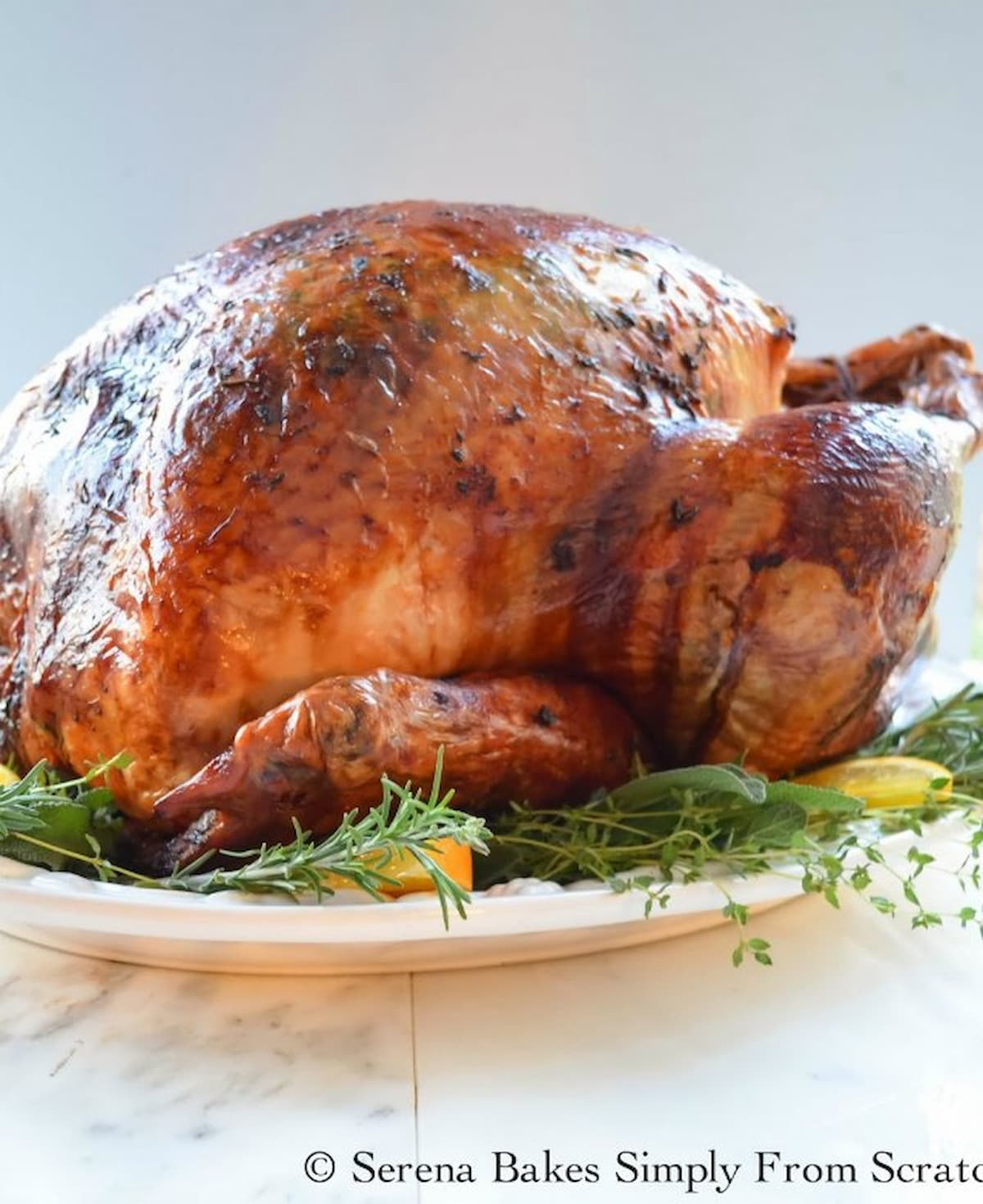 Roasted Cheesecloth Turkey with Herb Butter on a white plate with herbs around the edge and orange slices.