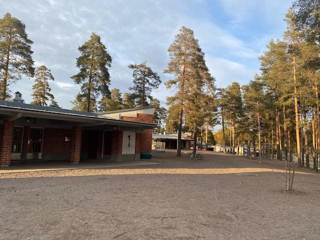 Koulurakennus ja sen pihapiiriä kangasmaastossa.