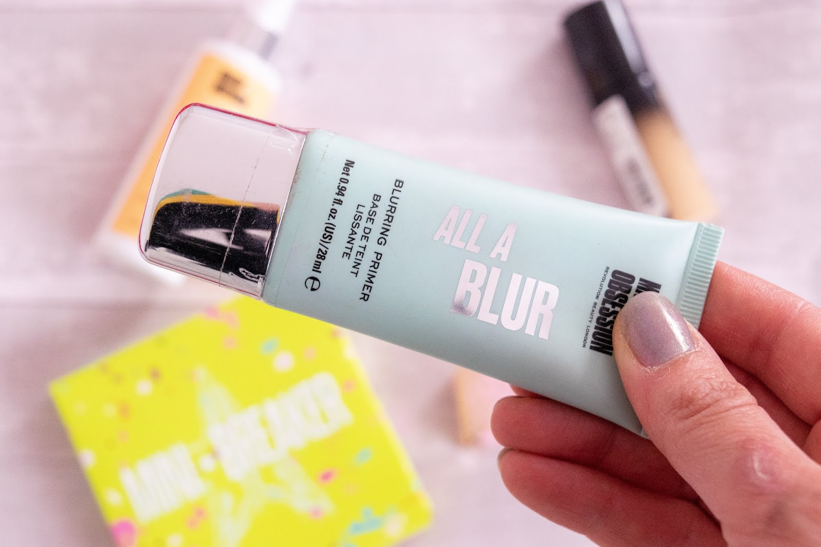 A close up of the Makeup Obsession Blur Primer. The tube is mint green with a silver cap.